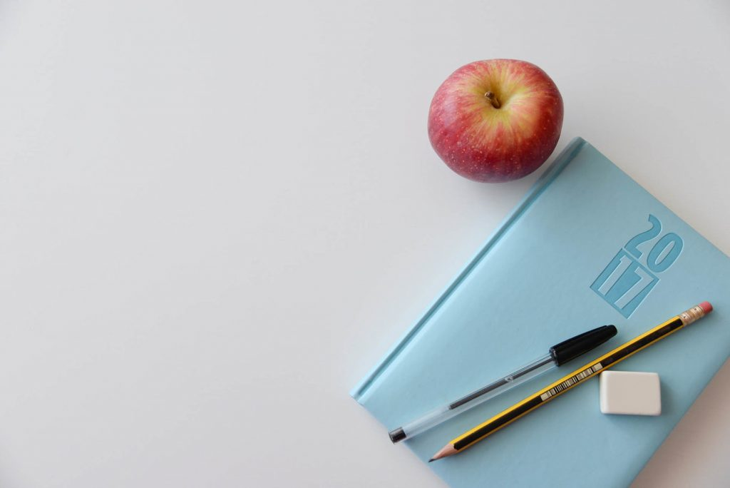 A Notebook, pen, pencils and an Apple to depict fundraising for kids